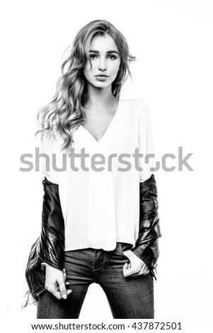 Portrait of young beautiful woman with black leather jacket. Long, light, wavy hair and makeup. - stock photo