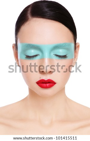Portrait of young beautiful woman with blue stripe painted on her face, over white background