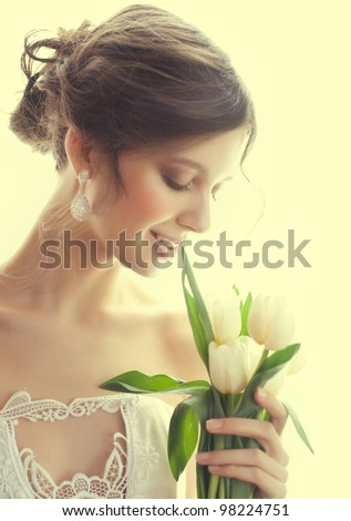 Portrait of young beautiful woman with bouquet of white tulips - stock photo