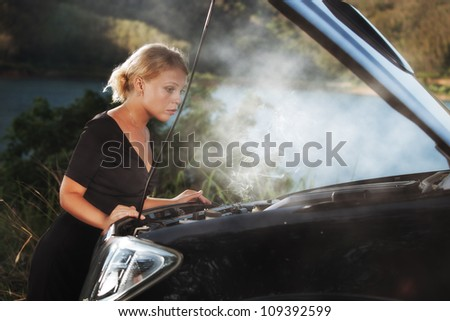 portrait of young beautiful woman with broken car aside - stock photo