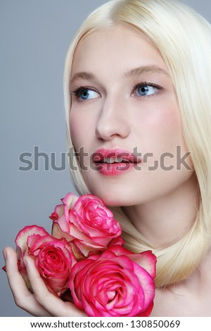 Portrait of young beautiful woman with clear make-up and fresh roses in her hand - stock photo