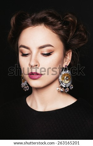 Portrait of young beautiful woman with closed eyes and big earrings. Makeup and pink lips. Dark background.