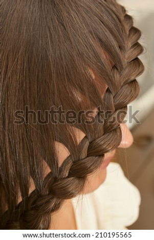 Portrait of young beautiful woman with creative braid hairdo - stock photo