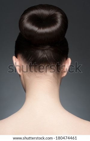Portrait of young beautiful woman with elegant hairstyle, hair bun. Rear view - stock photo