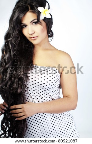 Portrait of young beautiful woman with extra long glossy hair - stock photo
