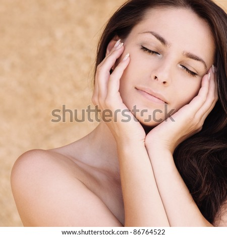 Portrait of young beautiful woman with eyes closed propping up her face against beige background. - stock photo