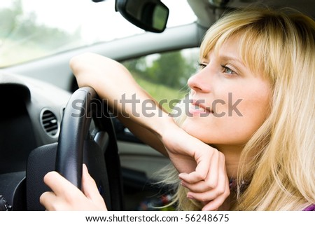Portrait of young beautiful woman with fair hair sitting in the car - stock photo