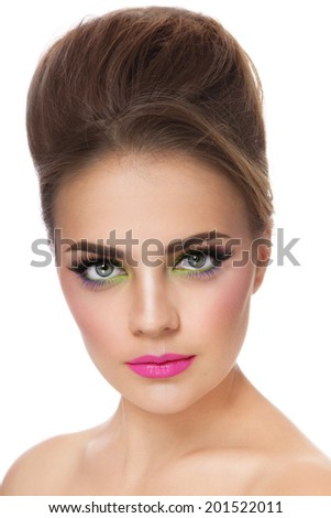 Portrait of young beautiful woman with fancy colorful make-up and hair bun, over white background - stock photo