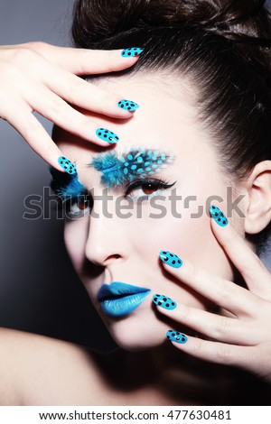 Portrait of young beautiful woman with fancy feather eyebrows and dot manicure