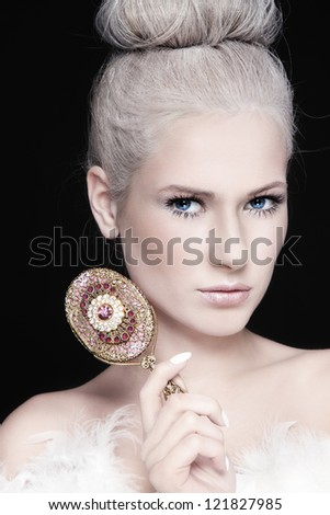 Portrait of young beautiful woman with fancy make-up and vintage mirror - stock photo