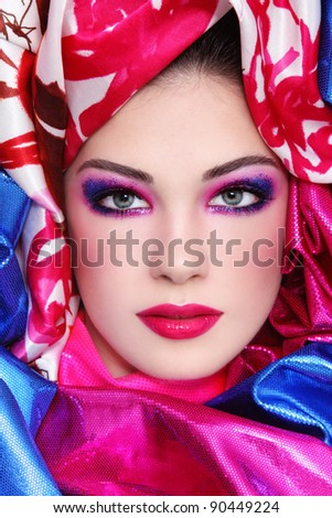 Portrait of young beautiful woman with fancy sparkly make-up and bright fabrics around her face - stock photo