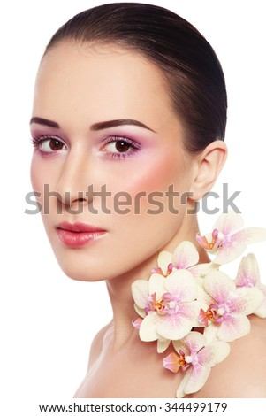 Portrait of young beautiful woman with glowing make-up and orchid over white background - stock photo