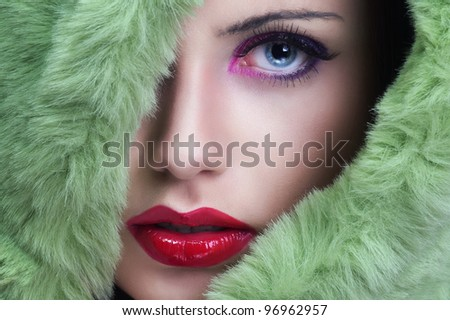 Portrait of young beautiful woman with green fur. - stock photo