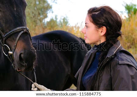 portrait of young beautiful woman with horse - stock photo