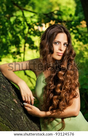 Portrait of young beautiful woman with long curly hair - stock photo