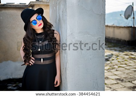 Portrait of young beautiful woman with long curly hair wearing a black dress, hat and glasses, posing, with copy space area for your text .Girl showing her gorgeous hair. - stock photo