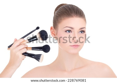 portrait of young beautiful woman with make up brushes set isolated on white background