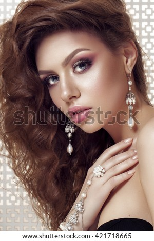 Portrait of young beautiful woman with perfect makeup and blue eyes touching her shoulder . Light background. Wearing pearls bracelet and earrings. - stock photo
