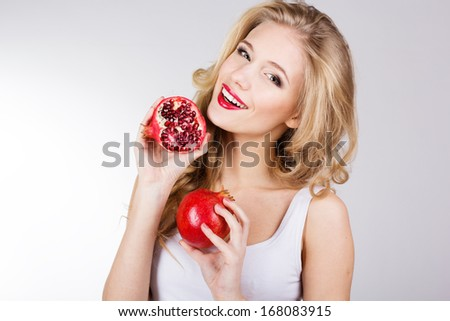 Portrait of young beautiful woman with pomegranates in her hands isolated on white background