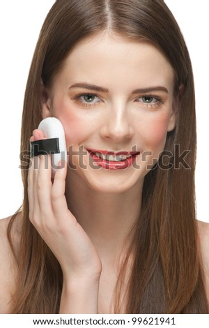 Portrait of young beautiful woman with powder puffs. Pretty woman applying make-up. - stock photo
