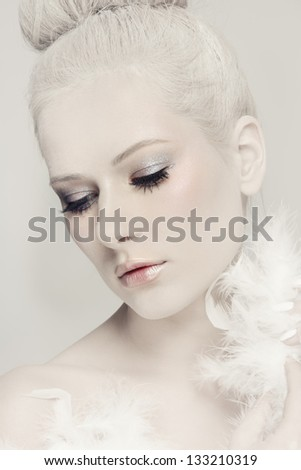 Portrait of young beautiful woman with powdered vintage hairdo and white feather boa - stock photo