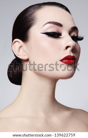 Portrait of young beautiful woman with red lips and cat eyes make-up - stock photo