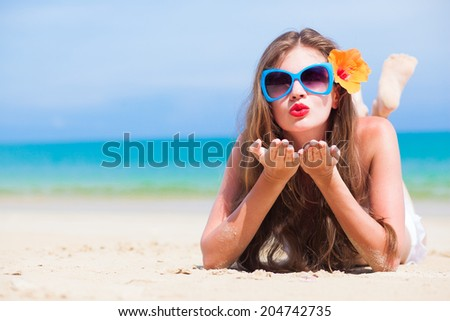portrait of young beautiful woman with red lips and hibiscus blowing air kiss - stock photo