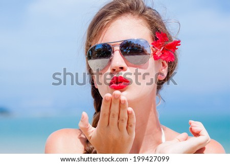 portrait of young beautiful woman with red lips blowing a kiss - stock photo