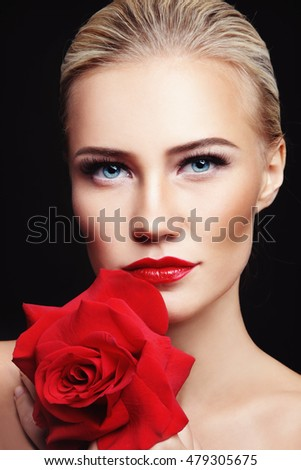 Portrait of young beautiful woman with red lipstick and rose in her hands
