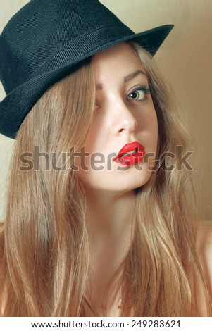 portrait of young beautiful woman with red lipstick in black hat.  filtered in warm tone - stock photo
