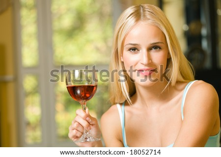Portrait of young beautiful woman with red-wine glass, indoors