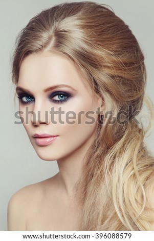 Portrait of young beautiful woman with smoky eyes make-up and stylish messy hairdo - stock photo
