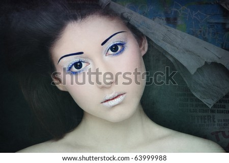 Portrait of young beautiful woman with sparkly futuristic make-up on grainy damaged vintage background - stock photo