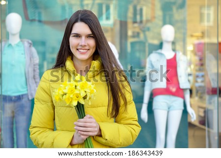 Portrait of young beautiful woman with spring flowers, outdoor over shopwindow with dummy. - stock photo