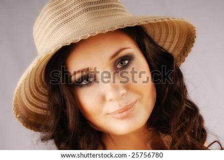 Portrait of  young beautiful woman with straw hat on  head in studio