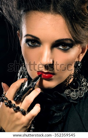 Portrait of young beautiful woman with stylish make-up and claw rings on her fingers - stock photo