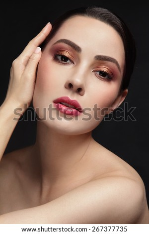 Portrait of young beautiful woman with stylish make-up touching her face - stock photo