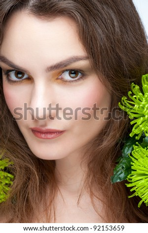 Portrait of young beautiful woman with stylish makeup and green flowers - stock photo