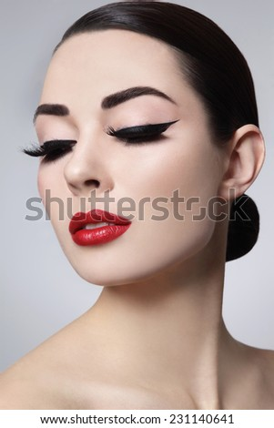 Portrait of young beautiful woman with stylish makeup. False eyelashes, black eyeliner and red lips - stock photo