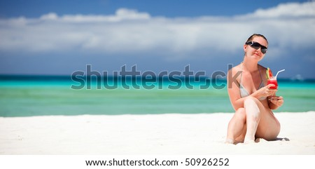 Portrait of young beautiful woman with tropical fresh juice - stock photo