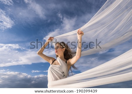 Portrait of young beautiful woman with waving fabric in her arms on wind