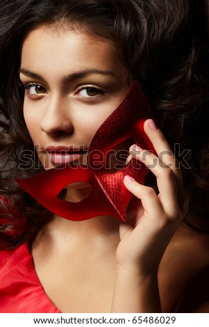 Portrait of young beautiful woman with with red carnival mask - stock photo