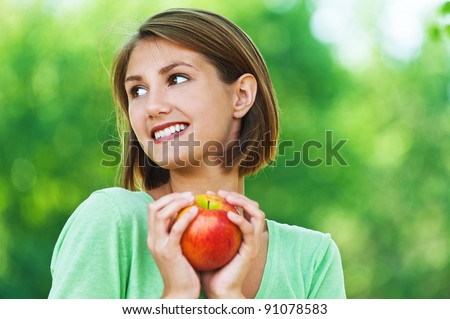 portrait of young, beautiful women - vegetarian holding an apple, looks away, against background of summer green nature - stock photo