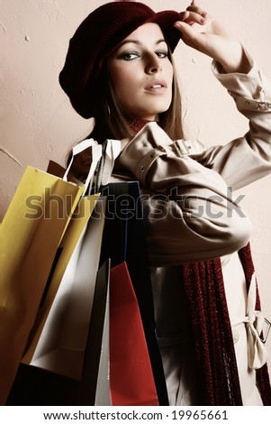Portrait of young beautiful women with her shopping bags (retro tones) - stock photo