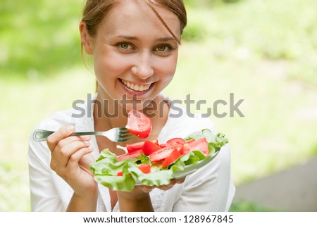 Portrait of young beauty woman eating salad - stock photo