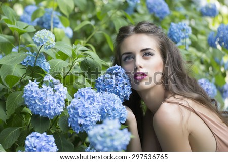 Portrait of young beutiful sensual girl with bright makeup and curly brunette hair sitting near lush blooming bush with blue flowers of hydrangea and green leaves looking away, horizontal picture - stock photo