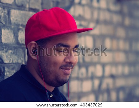 Portrait of young black boy listening to the music in headphones with smile. Good music provides good mood - stock photo
