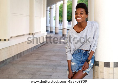 Portrait of young black female fashion model standing outdoors and smiling