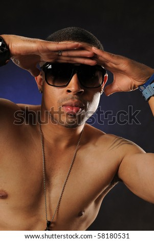 Portrait of young black man wearing sunglasses against a a dark background