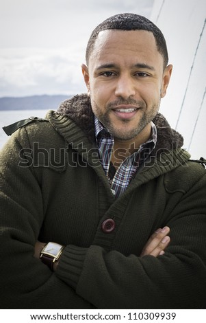 Portrait of young black man with smile and arms crossed standing on boat deck, leaning against wall with water in the background.